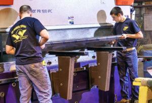 Workers bending metal